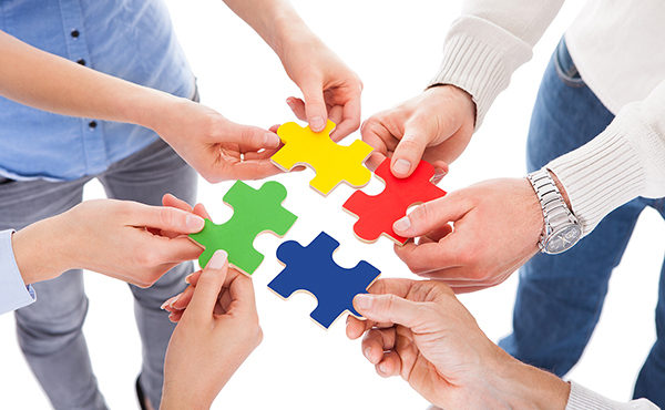 Close-up Of Five People Hand Holding Colorful Puzzle Over White Background